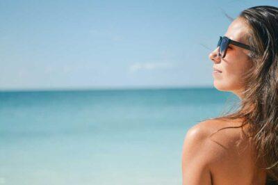 kobieta nad morzem wystawia twarz do słońca