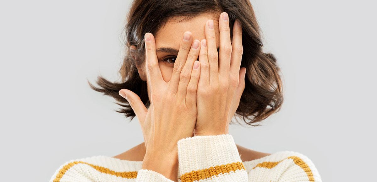 Młoda kobieta zasłaniająca twarz