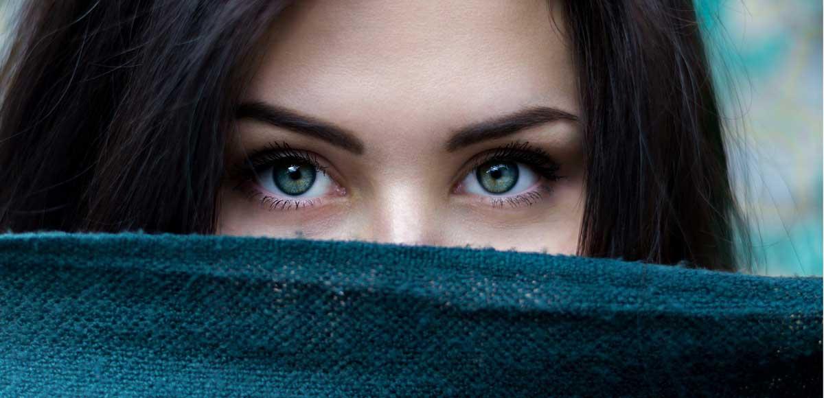 Twarz młodej kobiety z zasłoniętymi ustami i wyrazistymi oczami