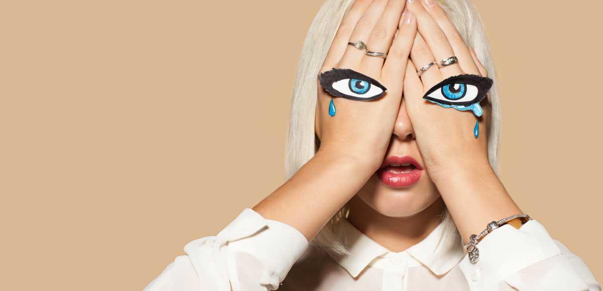 Kobieta zasłaniająca twarz z płaczącymi oczami na dłoniach
